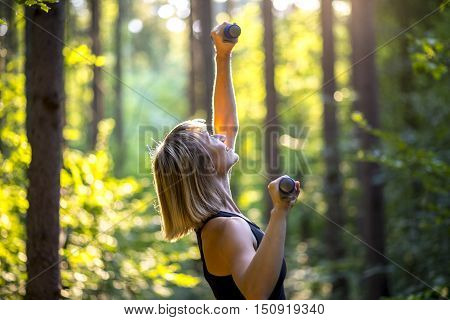 Sporty young woman working out with weights to tone and strengthen her muscles outdoors in sunlit woodland amongst the trees in a health and fitness concept.