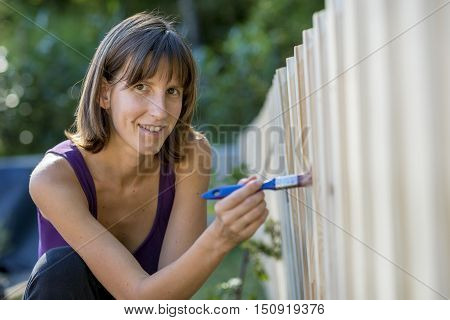 Smiling woman painting a garden fence with a paintbrush in a concept of DIY and yard maintenance.