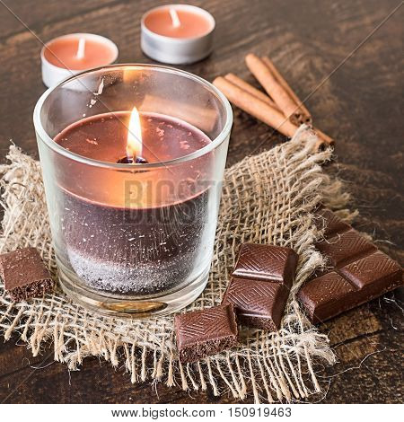 Scented decorative candles, chocolate bar and cinnamon sticks on brown wooden background.