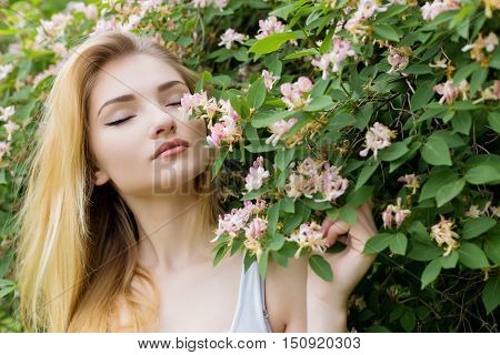 beautiful lovely girl with long blonde hair enjoying nature near blooming rosebush in a white t-shirt with full lips bright summer day