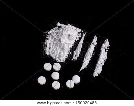 Cocaine drug powder pile and lines, pills on black background