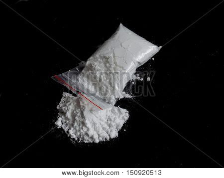 Cocaine drug powder in bag and cocaine powder pile on black background