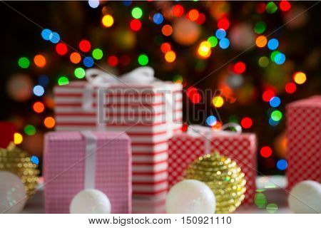 Christmas presents and balls against the backdrop of a festive Christmas tree