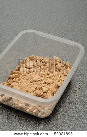 Crushed round biscuits in a plastic container