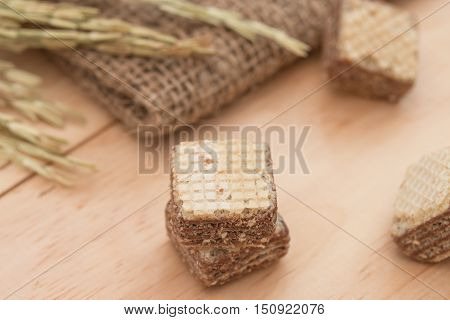 Wafers with chocolate on a wooden background.