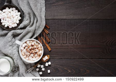 Wooden background with cap of cacao and marshmallow