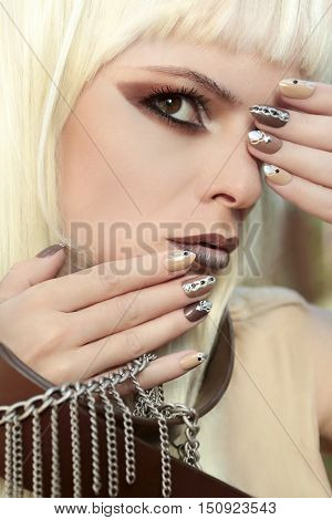 Makeup and manicure in brown and beige shades with a pattern of chains and rhinestones on very oval nails.