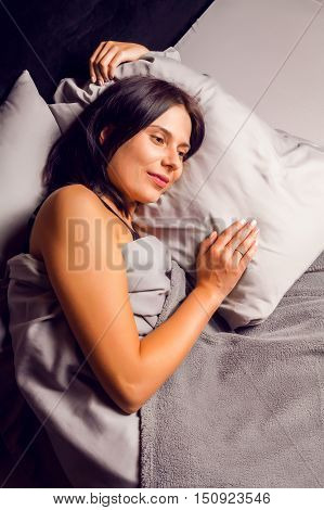 A woman with a smile on her face lying in bed on her side on a dark background. Beautiful young brunette sleeping sweetly in bed.