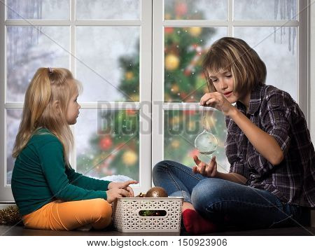 Children are preparing for the New Year Christmas. Girls sit at the window and consider Christmas decorations. Outside the window Christmas tree snow