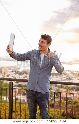 Young Man Pulling Faces At His Tablet
