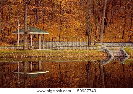 landscape beautiful park with arbour at fall autumn trees and lake reflection nobody gold foliage