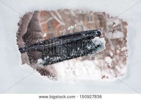 hand cleaning of car from the snow with brush