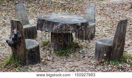 picnic area with chairs and table in park made of wood stub with foliage excellent place to rest