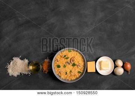 Risotto with mushrooms, fresh herbs and parmesan cheese. black chalkboard, top view horizontal orientation