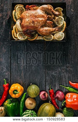 Whole chiken baked on metal tray and variety of fresh ripe autumn vegetable for Thanksgiving party table