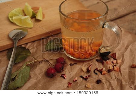 sea buckthorn tea in a transparent mug and a rose hip lime. useful warming winter drink.
