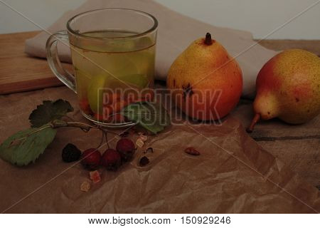 sea buckthorn tea in a transparent mug and a rose hip lime and pear. useful warming winter drink.
