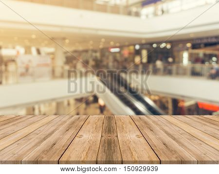 Wooden board empty table blurred background. Perspective brown wood over blur in department store - can be used for display or montage your products.Mock up for display of product.