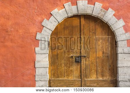 Medieval arched wooden door - Medieval building entrance with an arched double door made from hard wood