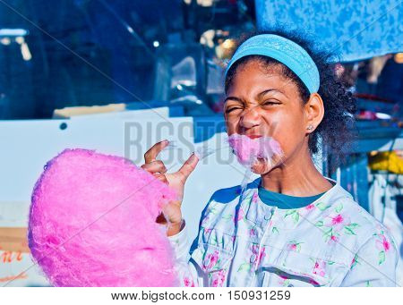 happy girl eats the hot cotton candy just prepared