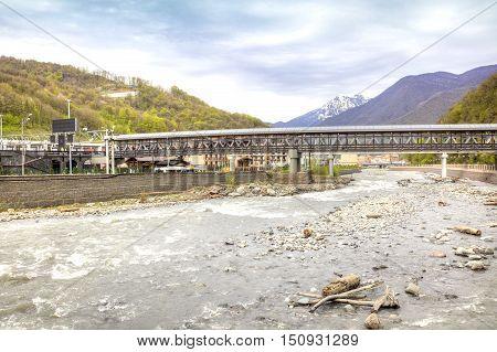 SOCHI KRASNAYA POLYANA RUSSIA - April 29.2015: Covered foot-bridge across the river Mzymta