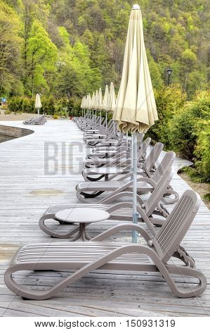 Empty deck-chairs by an early spring ashore artificial lake in the settlement of municipal type Krasnaya Polyana
