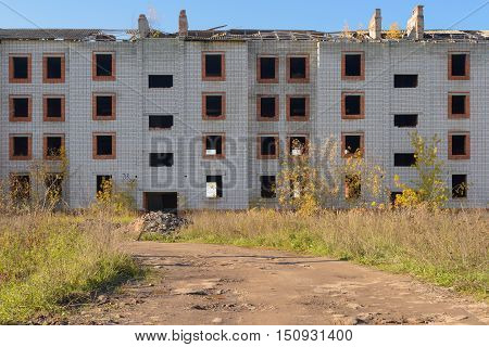 dilapidated abandoned brick apartment house among the fields