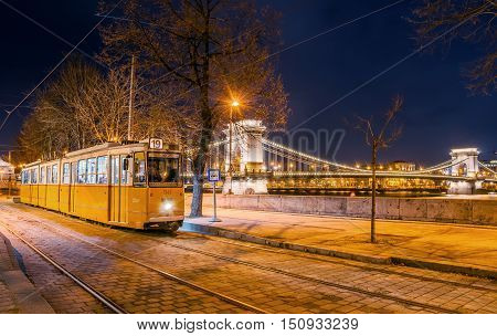 Night View Of The Tram On The Background Of The Chain Bridge In Budapest