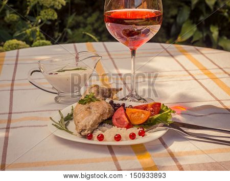 Gourmet roasted rabbit leg with rice and beans. White sauce and glass of red wine. Meal is served on white simply plate and checked table cloth with cutlery. Health and light meal good for diet.