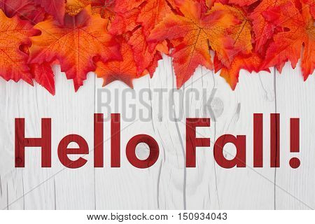 Hello Fall Greeting Some fall leaves on weathered wood with text Hello Fall