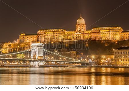 Night view of the Szechenyi Chain Bridge over Danube River and Royal Palace in Buda Castle in Budapest Hungary