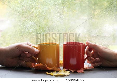 two hands holding cups on the background of wet window with raindrops / together tastier and warmer