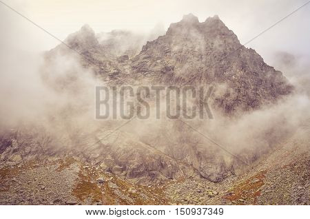 Cloudy mountain landscape. Rocky peaks in the clouds in High Tatra Slovakia.