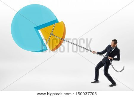 Businessman pulling a rope with a piece of the pie chart. Reduction in costs and outgoings. Hard work. Focus on results.