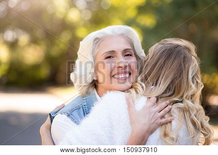 My little adult girl. Beautiful gray haired woman hugging her daughter and smiling while standing in the park.