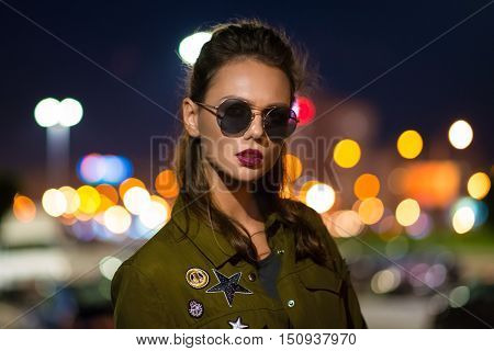 Beautiful woman standing on illuminated street at night.