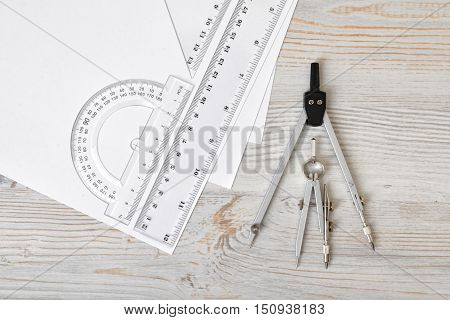 Layout with compass, protractor and centimeter ruler on wooden surface in top view. Workplace of draftsman, architect, constructor or designer. Engineering work. Measurement. Tools for drawing.
