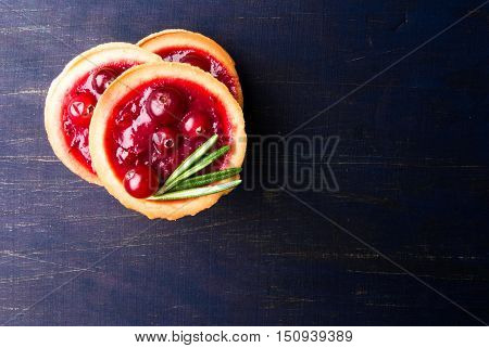 Winter one bite-sized snack or dessert: tartlets with sweet and sour cranberry sauce (jam), decorated with rosemary. Top view, copy space