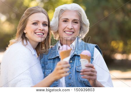 Would you like some ice cream. Satisfied pretty mother and daughter smiling and walking in the park while showing ice cream.