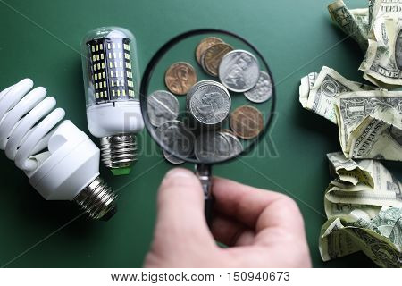 different lamps and money stack on a green table isolated