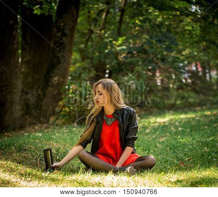 Beautiful Girl With Long Hair In Red Dress And Leather Jacket Sitting On The Grass