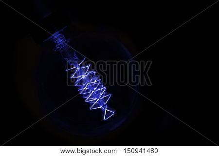 close up on blue light bulb glowing in dark
