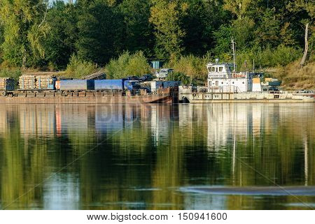 Malmyzh, Russia - September 3, 2009: The car ferry sails away from the coast to cross the Vyatka River.
