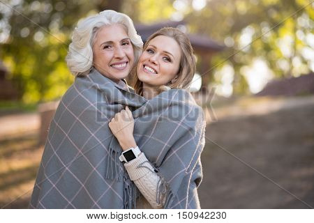 True love. Happy good looking mother and daughter smiling and covering with plaid while walking in a park.