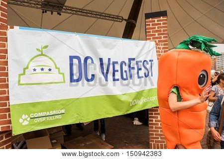 Washington DC, USA - September 24, 2016: VegFest vegan vegetarian festival and Compassion over Killing sign with carrot costume