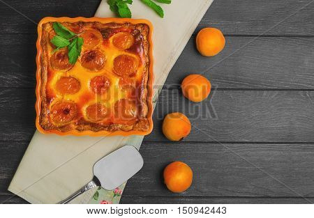 Fresh baked fruit pie Clafoutis tart with apricot cottage cheese. Apricot pie tart on the table sprig of mint cloth. Metal Shovel for apricot pie tart cake dark black wooden background. Top view.