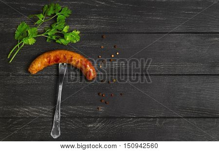 Meat Grilled homemade sausage on fork spices for grilled sausage parsley pepper peas dark black wooden background. Empty place for text. Top view.