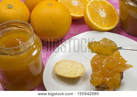 orange marmalade on the spoon, oranges on the table