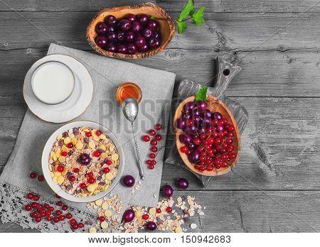 Morning breakfast muesli mix cereals dried fruits berries in bowl. Fresh red berries to muesli cereals cherries gooseberries redcurrants honey milk. Muesli berries scattered on table. Top view