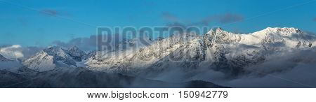Snow-covered mountains at sunrise. Greater Caucasus Mountain Range. Caucasus mountains. Karachay-Cherkessia. Russia.